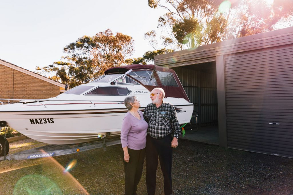 A couple standing in front of their boat